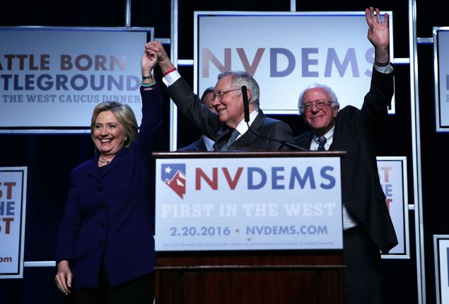 LAS VEGAS, NV - JANUARY 06:  Democratic Presidential candidates Hillary Clinton (L) and Sen. Bernie Sanders (I-VT) (R) on stage with Senate Minority Leader Harry Reid (D-NV) (2nd L) prior to the Battle Born/Battleground First in the West Caucus Dinner at the MGM Grand January 6, 2016 in Las Vegas, Nevada. The three candidates continue to campaign prior to the Nevada Democratic caucus, which will take place on February 20, 2016.  (Photo by Alex Wong/Getty Images)